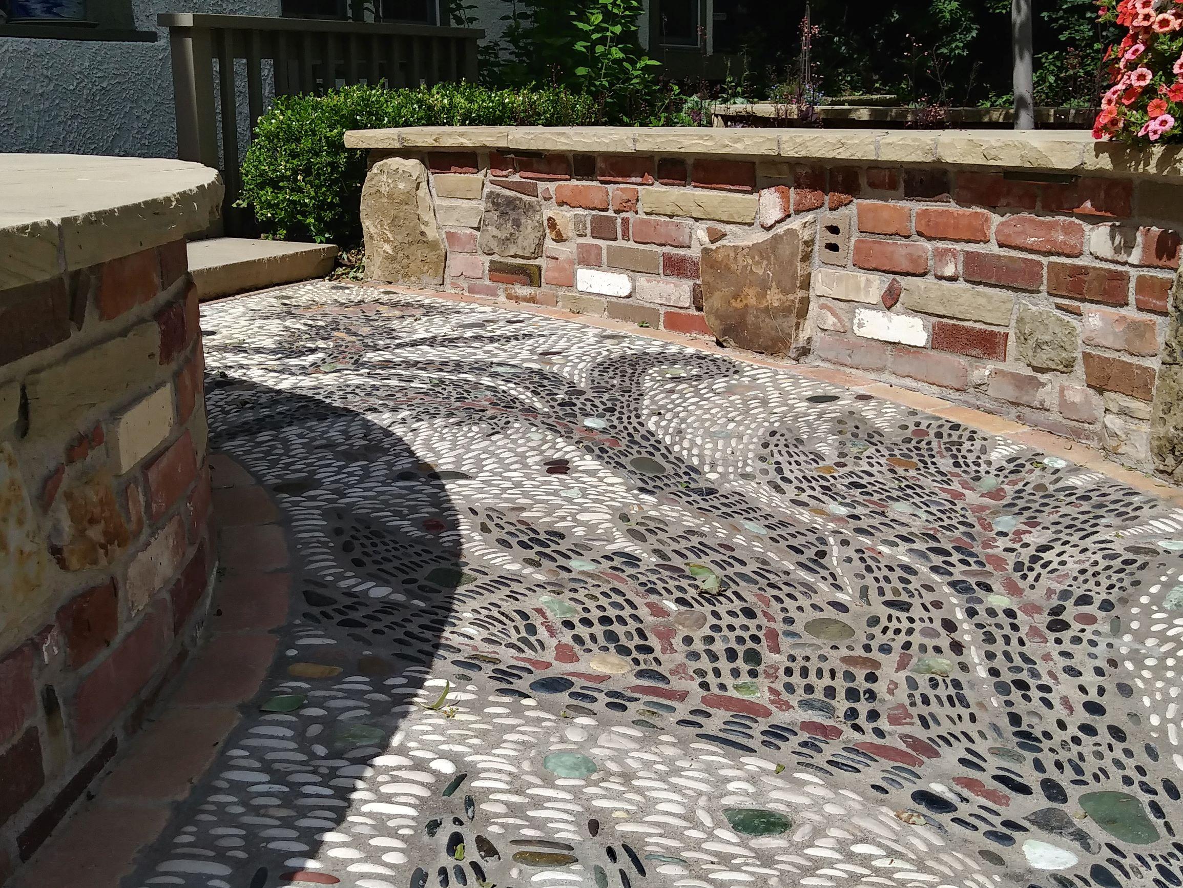 Small mosaic pathway with brick half walls and flat stone tops.
