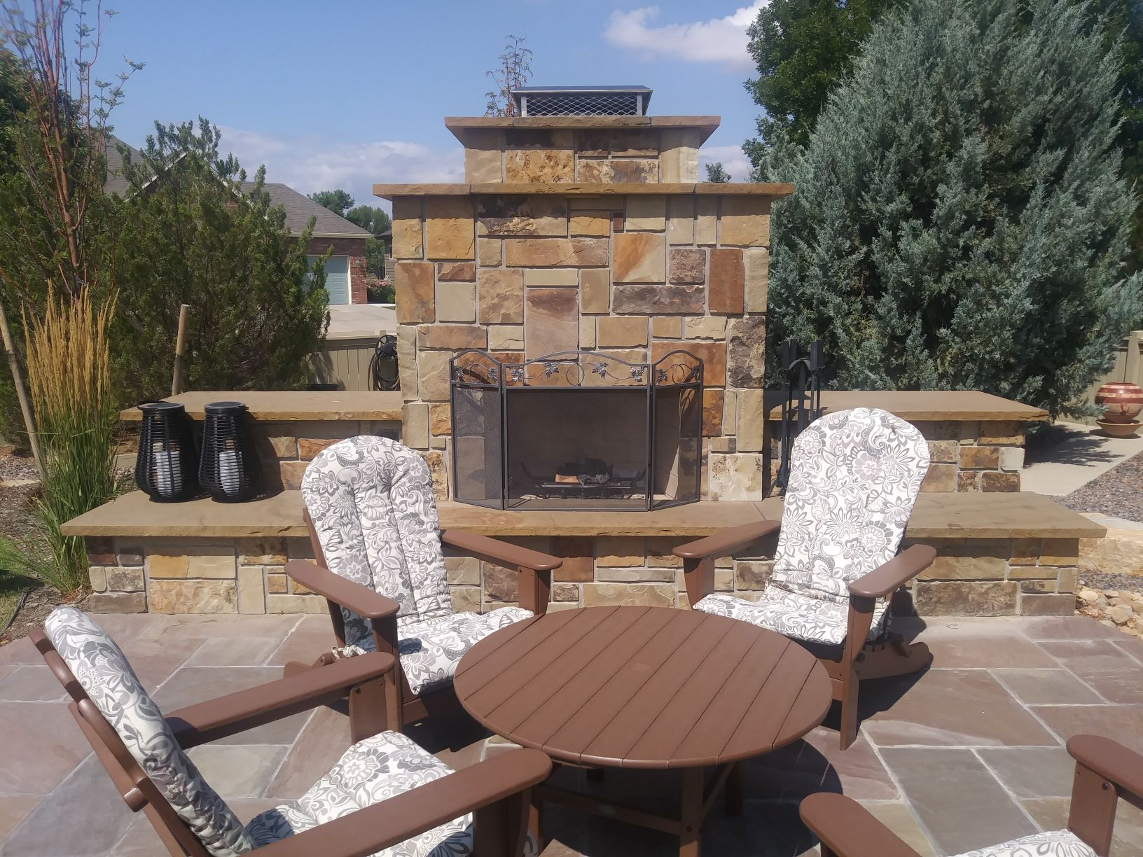 Outdoor Fireplace with large stone chimney and seating area in front.