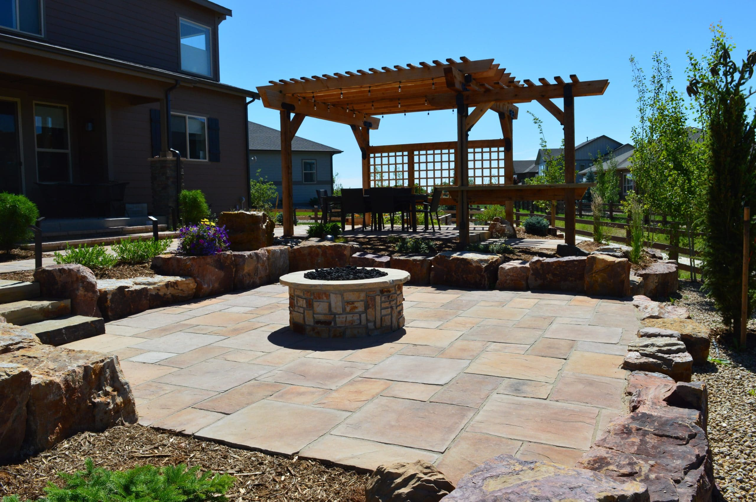 Stone patio with fire pit in the center. Pergola over top of a stone patio with seating underneath.