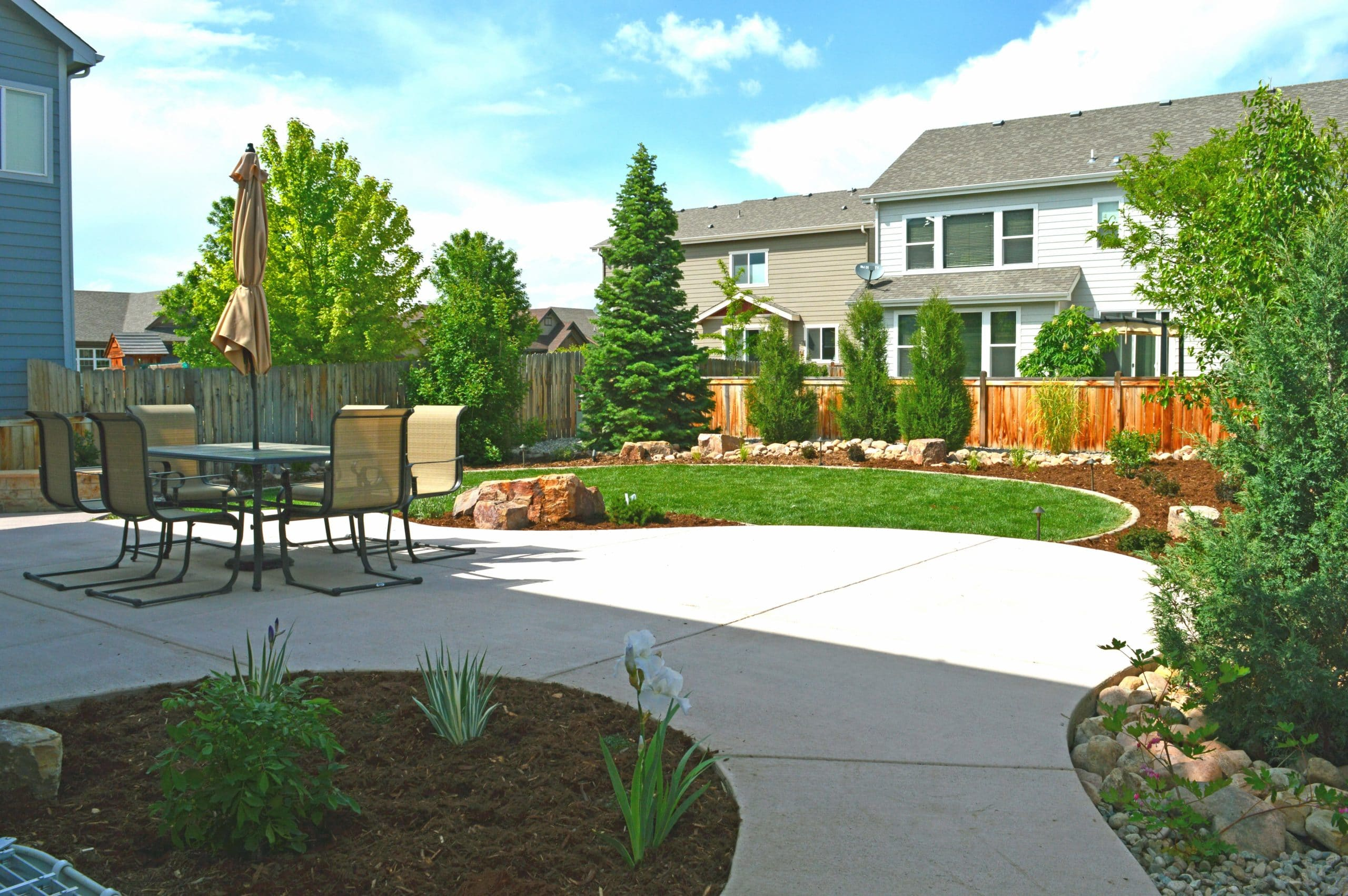 Concrete patio with concrete mow strip as well as mulch and large decorative rock filled with plants, bushes, and trees.