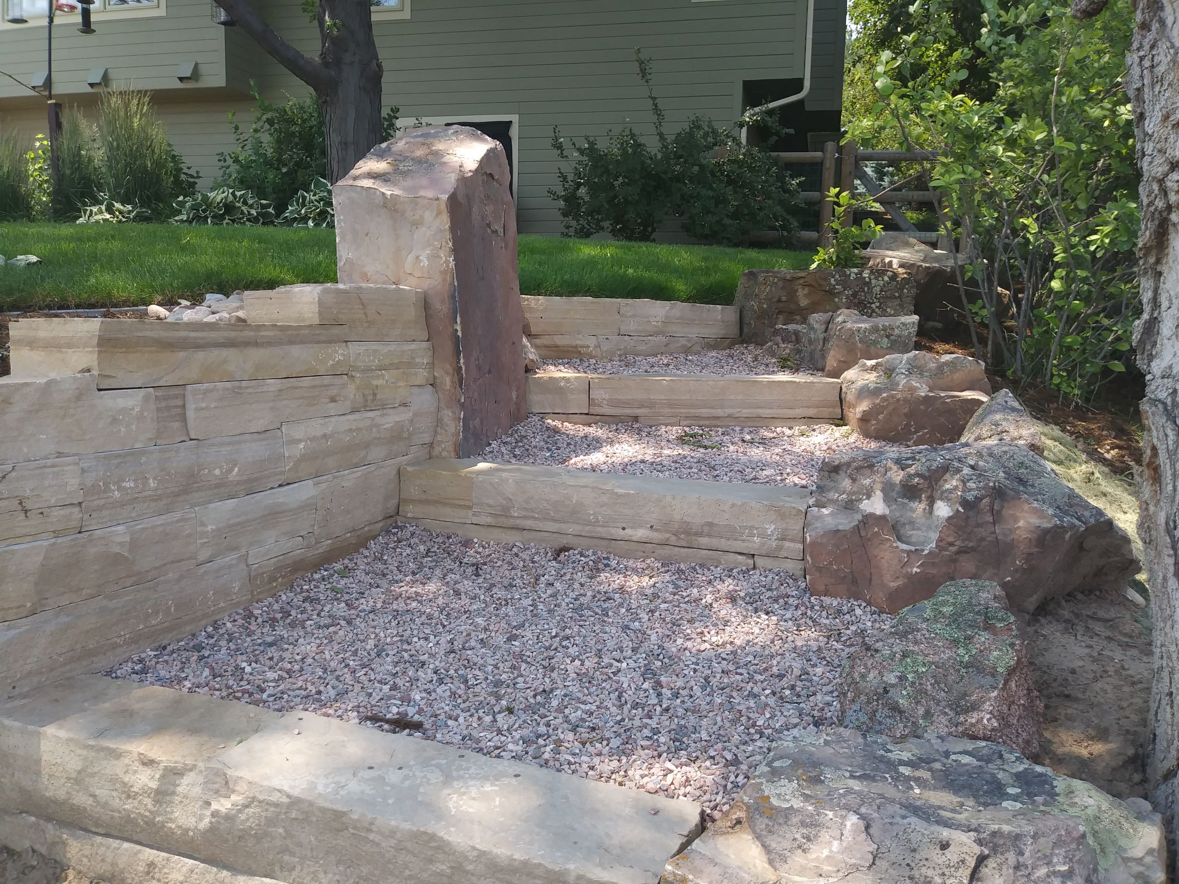 Gravel path with stone steps bordered with large decorative rock.