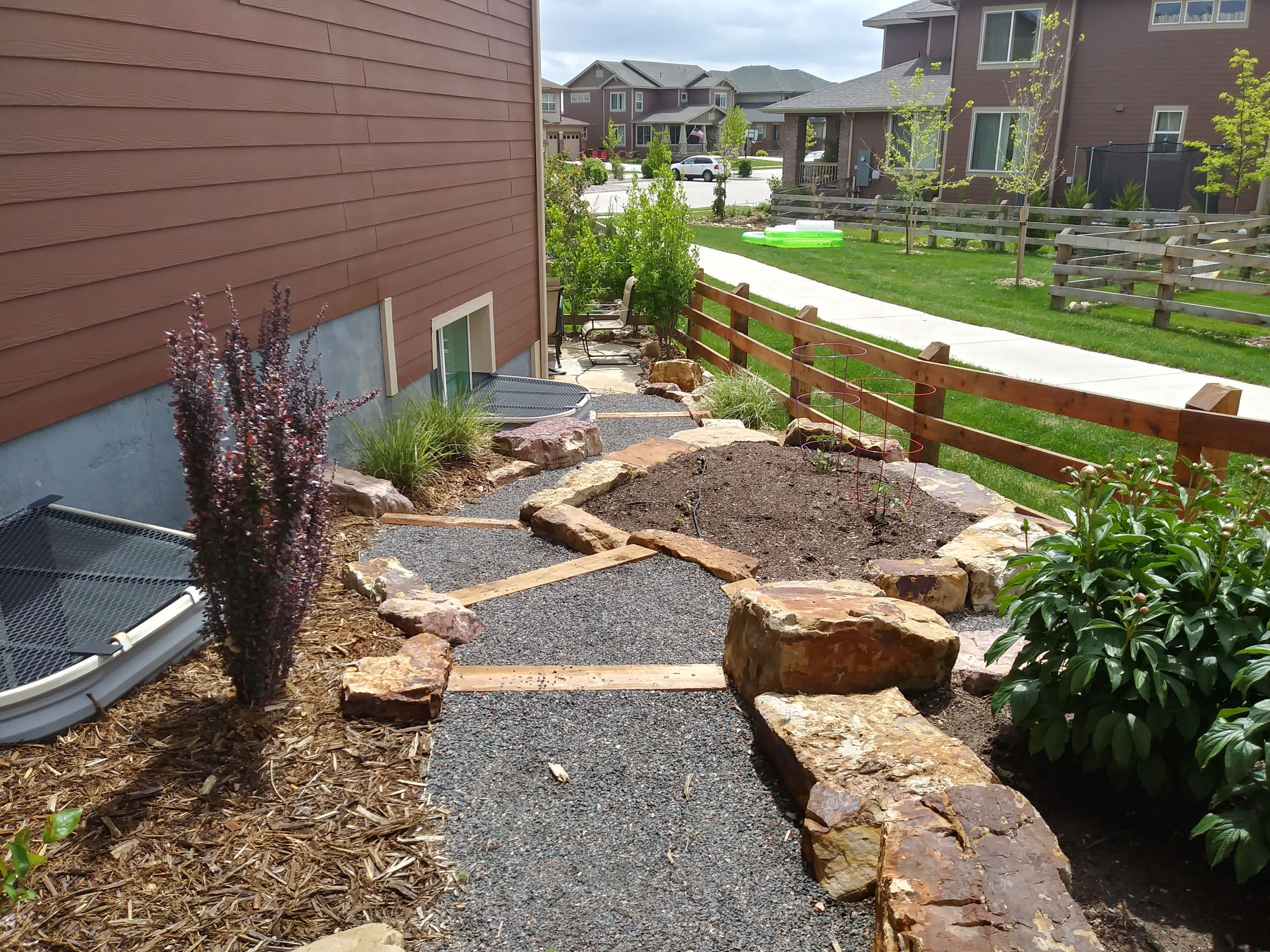 Gravel path with wood steps. Edged with large rocks and mulch beds with plants and bushes.