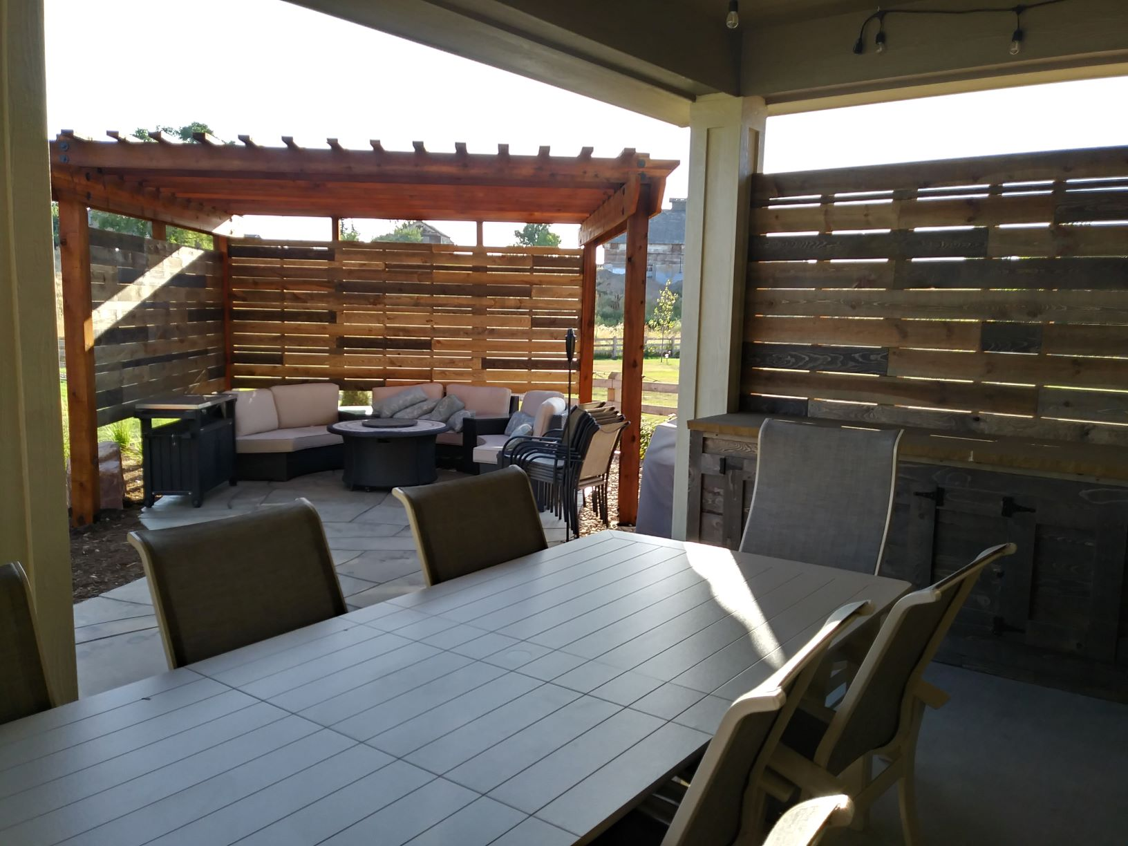 Pergola over flat stone patio with wall for privacy and wind control.