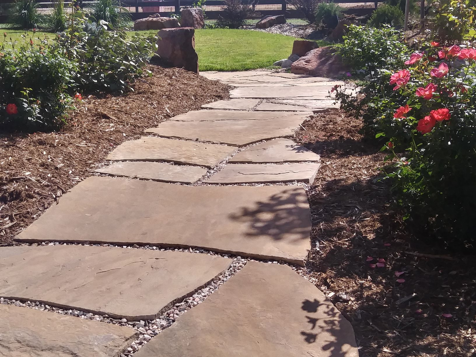 Flat stone path surrounded by mulch with colorful flowers and boulders.