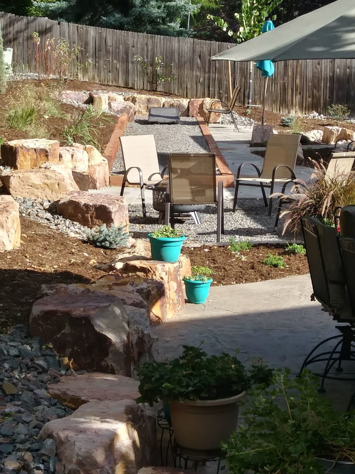 Backyard seating area with flat stone patio and gravel chair area. Surrounded by mulch with low water bushes and plants.