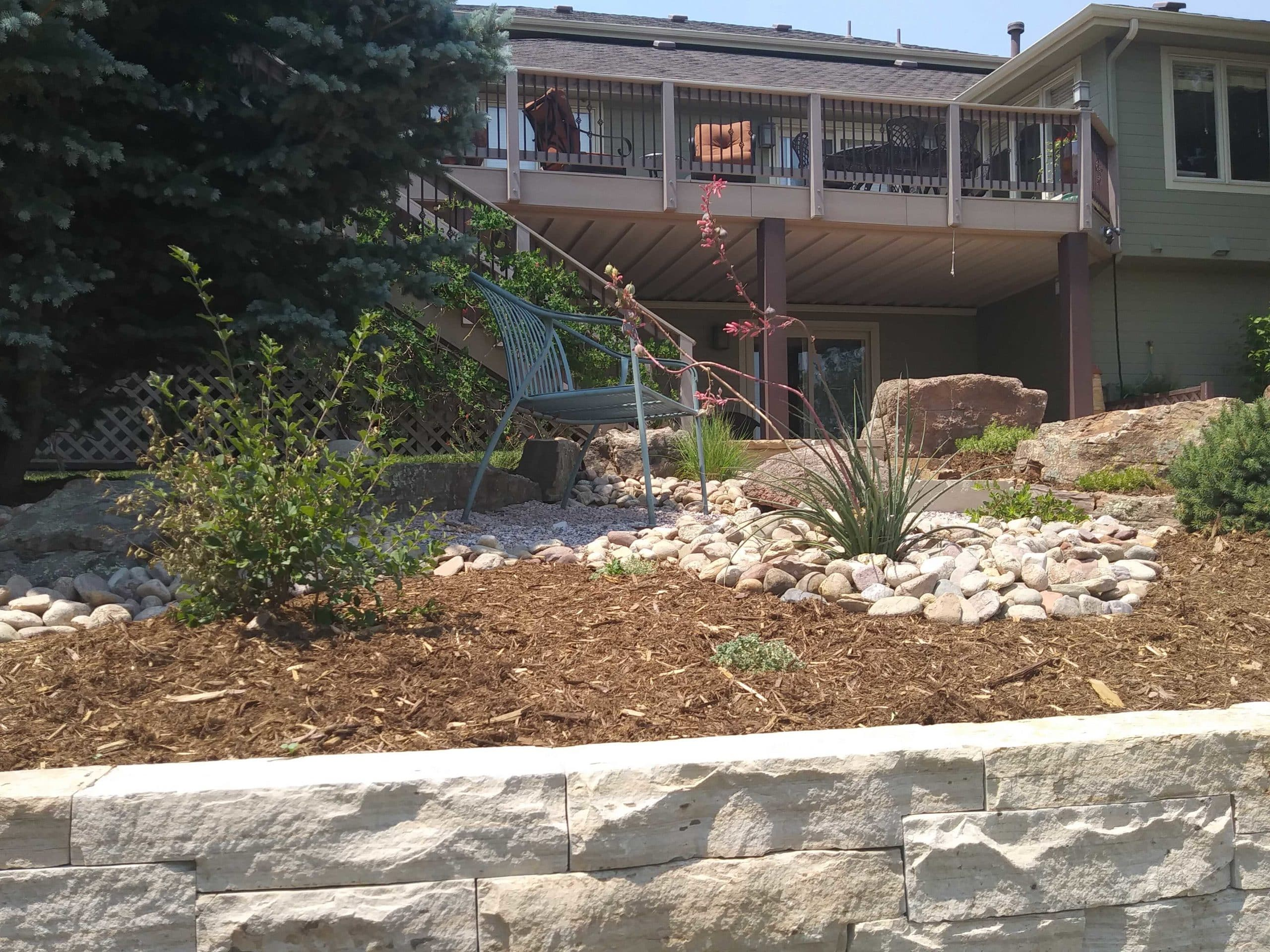 Backyard deck with rock, mulch, and gravel path to bench.